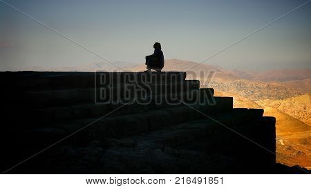 Sitting human silhouette next to stairs in Nemrut, Adiyaman Turkey
