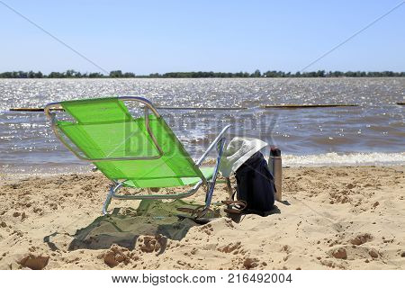 Green backpack, handbag, woman hat, thermo and sandals in the morning sun on the beach of the Parana river, Rosario, Santa Fe, Argentina.