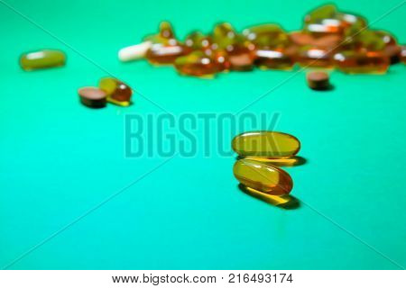Background of assorted pharmaceutical capsules and medication in different colors on green background. Medication concept.