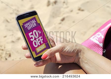 Young woman resting on the beach in the sun with a smartphone where she reads 50% off advertising on the screen.  Marketing, ecommerce, cell phone publicity.