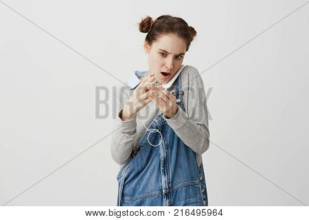 Caucasian lady with fashion hairstyle holding smartphone with shoulder while unraveling earphones. Girl having little trouble after carrying gadget in pocket. Situation and solution