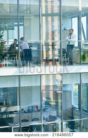 Wide angle portrait of mature businessman speaking by phone standing behind floor to ceiling windows in modern office building, copy space
