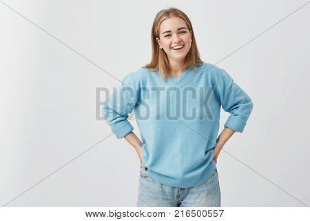 Happy smiling female with attractive appearance and fair hair wearing blue sweater and jeans showing her broad smile having good mood liking to pose at camera, putting her hands on her hips.