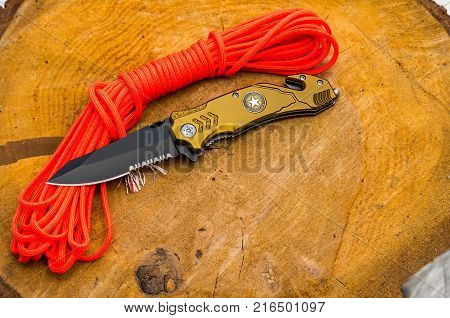 Knife for everyday carrying. Knife with tools for survival. Orange rope.