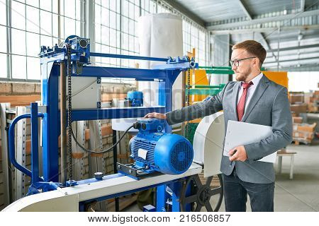 Portrait of successful salesman wearing suit posing next to brand new  machine units  in industrial  showroom
