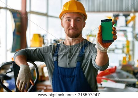 Portrait of cheerful young worker wearing hardhat posing looking at camera and holding smartphone with blank green screen while working at modern factory