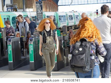 BRIGHTON GREAT BRITAIN - JUN 19 2017: Readhead girl and others walkingout from the train station in Brighton UK. June 27 2017 in Brighton Great Britain