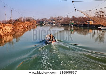 Ravenna, Emilia Romagna, Italy: landscape of the wetland in the nature reserve Po Delta Park, with fisherman in the boat on the river and fishing huts