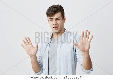 Offended caucasian young male has rush reaction on what he heard, raises hands, like saying stop that, has displeased and angry expression, isolated against gray background. European man with dark hair dressed in blue shirt expresses negative emotions