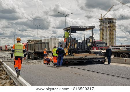 Tyumen Russia - June 1 2017: JSC Mostostroy-11. Construction of two-level outcome on bypass road on Fedyuninskogo and Permyakova streets intersection. Asphalt road paver paving machine