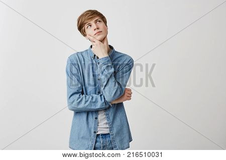 Shot of pensive young man with fair hair and blue eyes, has serious facial expression, looks up, keeps fingers under chin, being deep in thoughts, thinks about future plans. Thoughtful caucasian guy in denim shirt