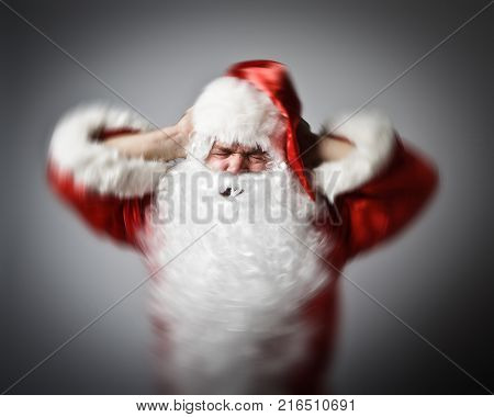 Frustrated Santa Claus. Santa Claus suffering from headache. Migraine concept. Blurred picture.