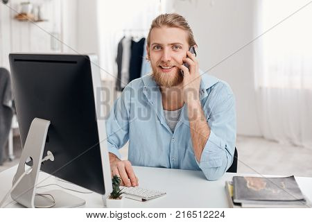 Cheerful smiling bearded male student recieves call from friend, sits at light office, dressed in blue shirt, finishes work soon. Handsome male freelancer has phone conversation with customer, discusses ideas.