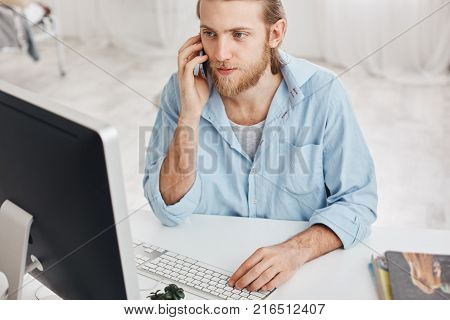 Business, office and technology concept. Bearded employee with fair hair, wearing blue shirt, talking on phone, communicating with his companions, typing on keyboard, looking on computer screen, using modern devices