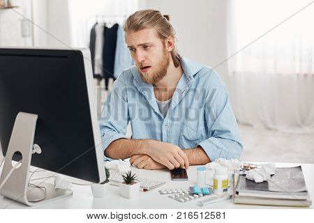 Portrait of ill or sick bearded male dressed in blue shirt with tired and suffering face expression, being allergic, having health problems.Young man has running nose, sits at workplace with pills and drugs
