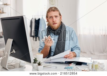 Portrait of ill bearded man sneezes, uses handkerchief, feels unwell, has flu. Sick male office worker has fever or allegic, has tired expression, discusses working issues with colleagues. Unhealthy lifestyle, illness and infection concept