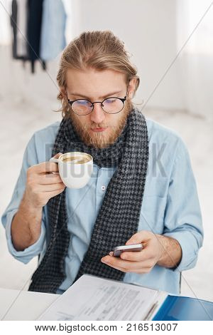 Bearded male office worker in round spectacles dressed in blue shirt and scarf, surrounded with papers and documents, recieves business message on smartphone, types answer, drinks coffee during break.