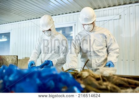 Portrait of two workers  wearing biohazard suits working at waste processing plant sorting recyclable materials on conveyor belt