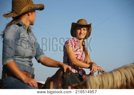 Country girls - women riding horse. Two young country girls sitting on horseback, looking at each other, talking, smiling.