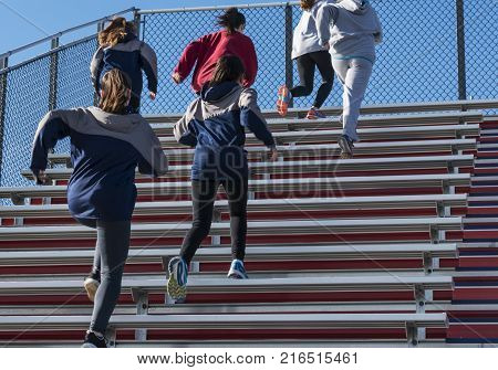 A high school girls track and field team running up the bleachers on a cool fall afternoon.