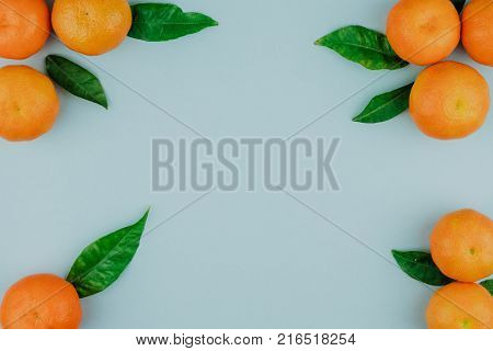 Violet backgroung with mandarins and mandarin leaves . Top view. Citrus background. Citrus mandarins frame with copyspace