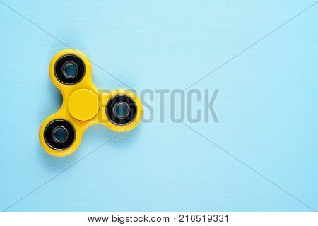 Fidget spinner toy on blue background top view