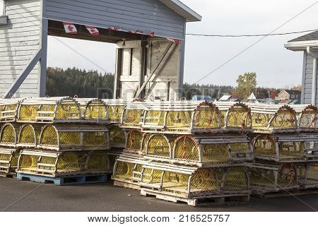 Wooden lobster traps stacked on pier along shoreline of Prince Edward Island Canada.