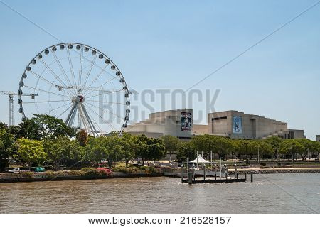 Brisbane Australia - December 8 2009: Rall Ferris Wheel adjacent to Performing Arts Centre along the river under light blue sky. Lyric Theatre performance banners. Green shoreline.