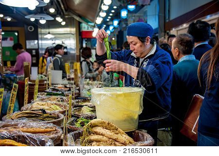A CROWDED MARKETPLACE. YOUNG VENDOR ADDS MORE PICKLES TO HIS STAND. Nishiki Market, Kyoto, - October 22, 2016: A crowded marketplace. Young vendor is adding more pickled vegetable to the stand. There are assortments of pickle varieties in his store.