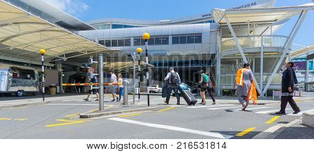 AUCKLAND NEW ZEALAND - NOVEMBER 23 2017 People including Indian woman in orange sari crossing road towards entranance to international airport terminal.