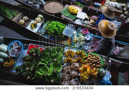 Old lady boating to trade food Floating market Damnoen Saduak District Ratchaburi Thailand