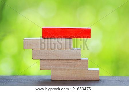 Stacked wooden bar with red wooden bar on the top.