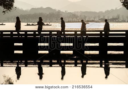 HANGZHOU, CHINA - FEB 10, 2015 - Five tourists in silhouette cross a bridge at Hangzhou's West Lake scenic area. West Lake is one of Eastern China's most famous attractions.