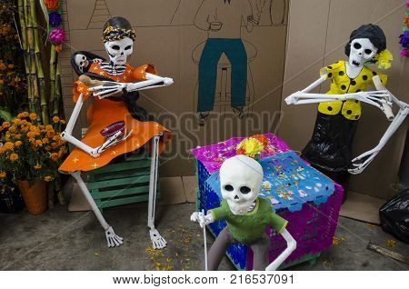 OAXACA, OAXACA, MEXICO- OCTOBER 30, 2017: Family of skulls and cut paper as decoration for mexican Day of the Dead celebration in Oaxaca, Mexico