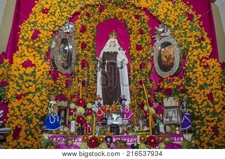 OAXACA, OAXACA, MEXICO- OCTOBER 30, 2017: Traditional offering altar with flowers, religious images, food and candles as decoration for mexican Day of the Dead at a restaurant in Oaxaca, Mexico