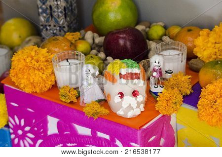 OAXACA, OAXACA, MEXICO- NOVEMBER 1, 2017: Mexican Day of the Dead offering altar with sugar skull, cut paper, flowers and fruits in Oaxaca, Mexico