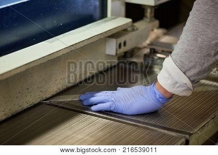 Worker is thrusting a metal sheet. Worker is thrusting a metal sheet to the guillotinen shear machine.