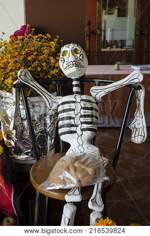 OAXACA, OAXACA- NOVEMBER 2, 2017: Skeleton sitting down with a piece of bread on his legs as decoration of mexican Day of the Dead in Oaxaca, Mexico