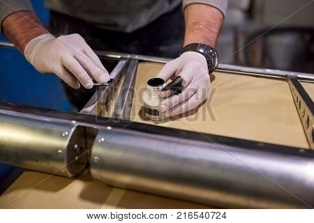 Hands of worker priming metal. Steel and primer. Anti rust coating.