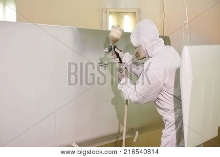 Spray painting, airplane wing. Worker in coverall using airbrush.