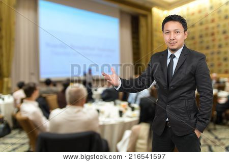 Asian Businessman with welcoming gesture on Abstract blurred photo of conference hall or seminar room with attendee background