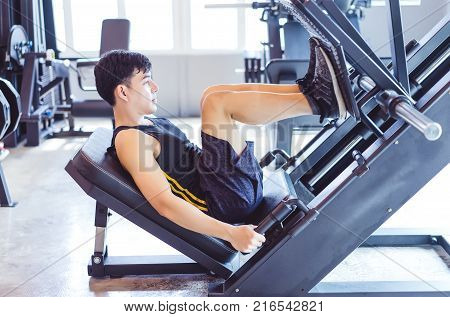 Handsome muscular man working out with leg press to define his upper leg muscles at the gymFitness and Healthy Lifstyle Concept.