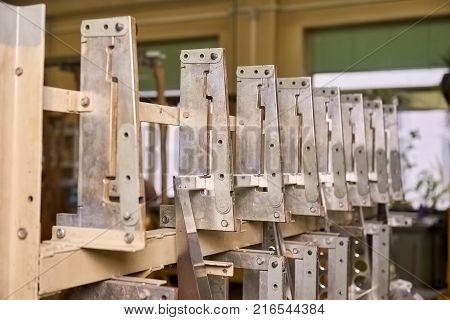 Row of identical metal details. Row of identical metal details attached to a framework.