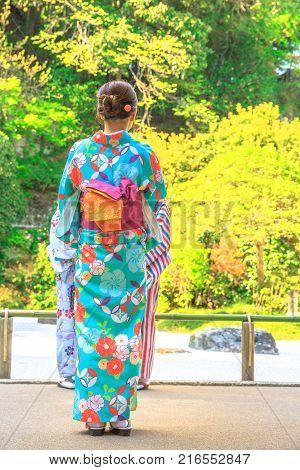 Hanami in spring season. Unidentifiable woman wearing Japanese kimono standing in the garden of Take-dera or Hokoku-ji Temple in Kamakura, Japan. Japanese culture.