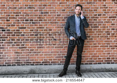 Young business man talking on the phone using mobile app for call with brick wall urban background. Happy caucasian businessman, professional in his 30s.