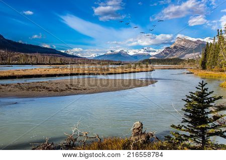 The sunny autumn in the Rockies of Canada. Delightful reservoir Abraham lake. Concept of ecological and active tourism