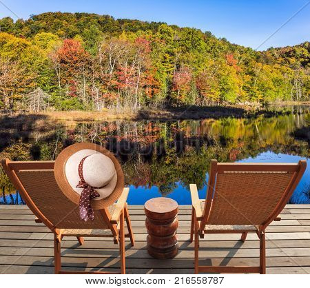 Wooden comfortable loungers on the shore of the pond. Foliage of forests is reflected in the pond. Magnificent resort in French Canada - Mont Tremblant. Concept of ecological tourism