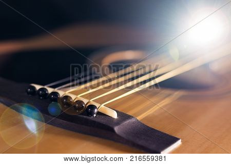 Close-up of rosette and strings of the acoustic guitar on black background.
