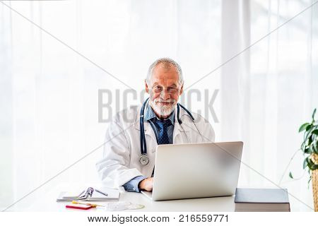 Senior male doctor working on laptop at the office desk.