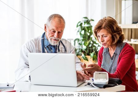 Male doctor with laptop talking to a senior woman in his office.